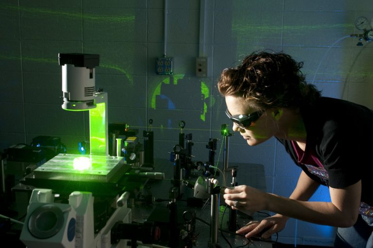 Researcher adjusts a laser for fluorescence immunoassay